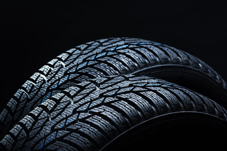 Set of new winter tires on black background with contrasty lighting.