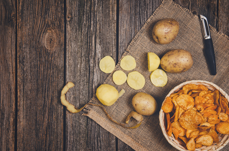 Heap of potato chips in vintage bowl on old wooden table