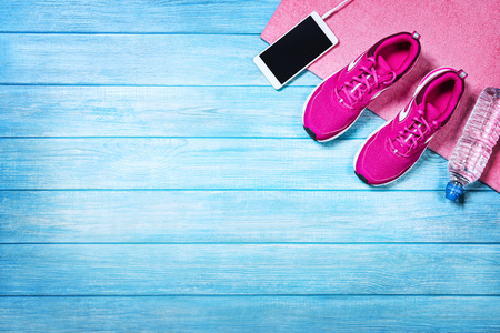 Fitness shoes over blue planks background. Sport shoes and accessories for sports activities on blue modern wooden floor, top view.