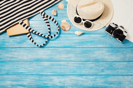Top view of blue planks marine pier near the beach. Frame composition with summer accessories. Background with copy space and visible wood texture. Border composition