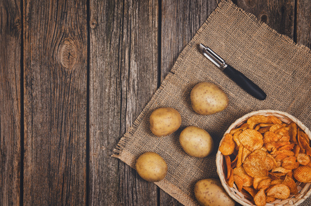 Heap of potato chips in vintage bowl on old wooden table background close-up with copy space for your text Imagens