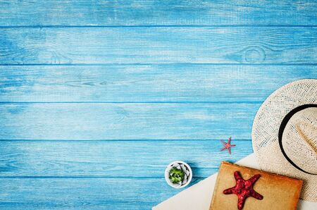 Zubehör für Reisedraufsicht auf blauem Holzhintergrund mit Kopierraum. Abenteuer- und Fernweh-Konzeptbild mit Reisezubehör. Vorbereitung auf eine exotische Reise, Reise und Sightseeing.