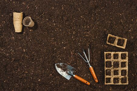 Gardening tools on soil texture background top view. Banco de Imagens