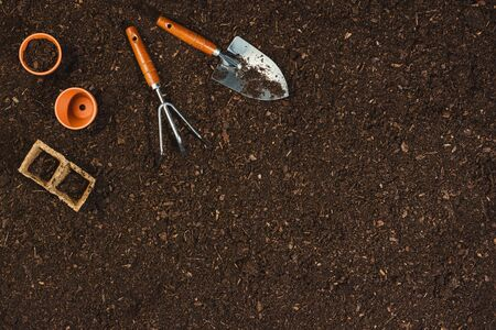 Gardening tools on fertile soil texture background seen from above, top view. Flat lay gardening or planting concept. Working in the spring garden. Banco de Imagens