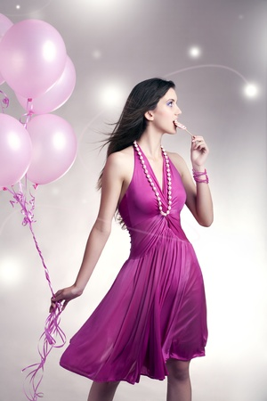 Girl standing with balloons and lollipop  Stock Photo
