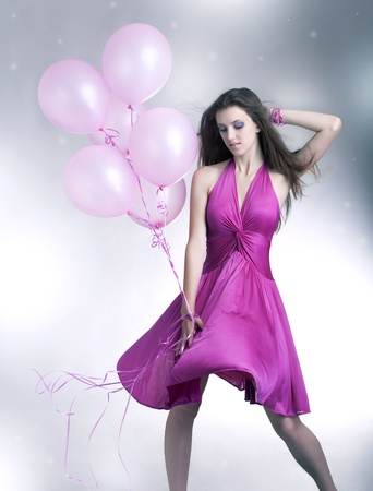 Girl standing with balloons photo