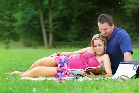 Pregnant woman with his husband in park