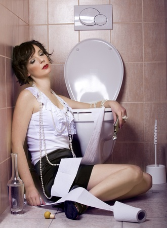 drunken: Drunk woman sitting dizzy on the toilet floor