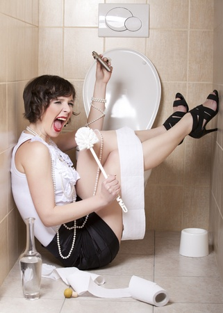 Drunk woman sitting dizzy on the toilet floor