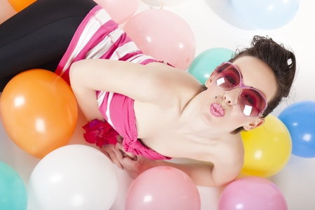 Party girl lying with balloons on the floor in colourful clothes