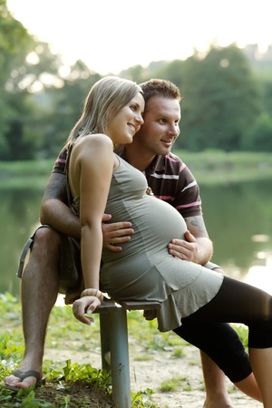 Happy pregnant woman with his husband at beautiful sunny day in park  Stock Photo