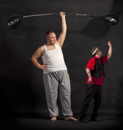 kidding: Strong man lifting a balloon barbell on the stage  Stock Photo