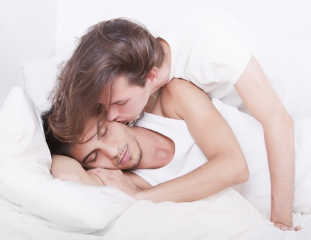 Gay couple kissing on the bed photo