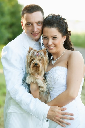 Bride and Groom similing with a dog  photo