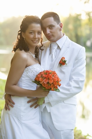 Bride and Groom smiling outdoors photo