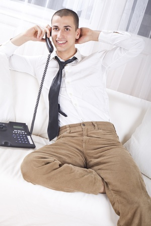 Young businessman sitting on couch talking on phone, smiling photo