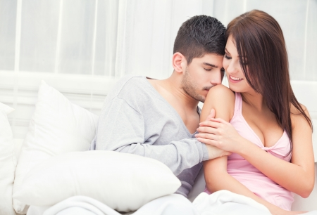 Lovely young couple sitting together on couch at home