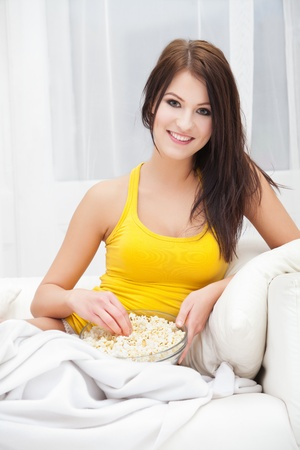 Young woman eating popcorn and watching TV at home Stock Photo