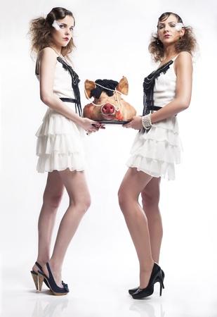 Young girls serving a pig head Standard-Bild