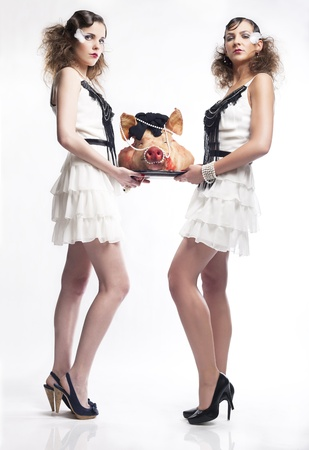 flesh: Young girls serving a pig head Stock Photo