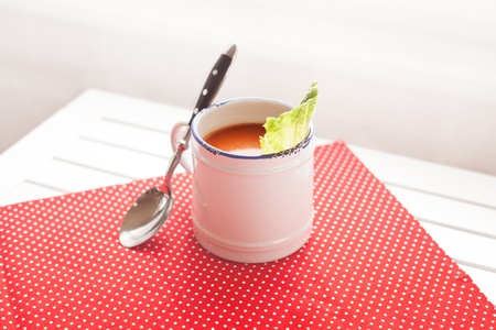 Tomato soup on a red cloth with a spoon Stock Photo