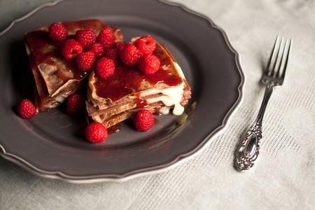 Chocholate raspberry pancake dessert on an table cover. Standard-Bild