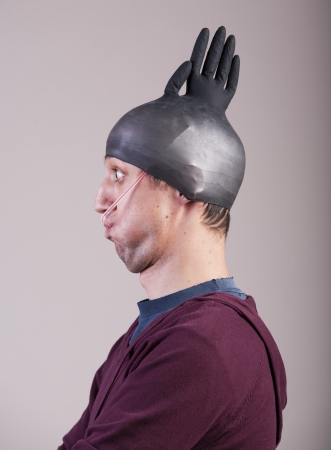 Funny man with a rubber glove on his head Imagens