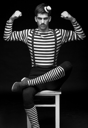 Morose circus performer sitting in a striped dress photo