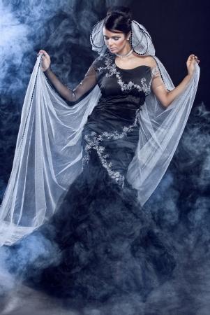 Beautiful woman standing in elegant fashion dress