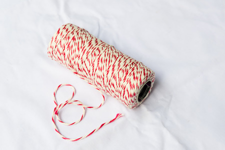 baker's: Red and white bakers twine spool on white cloth