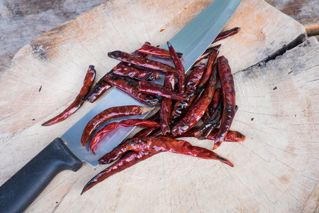 varkala: Drying the red hot chili pepper with knife  on the chopping block Stock Photo