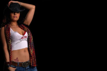 Beautiful latino girl with a hat posing over black (copy space) Stock Photo