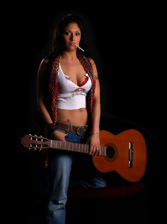Beautiful latino rock chick with an acoustic guitar and a cigarette in her mouth photo