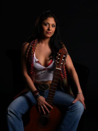 Beautiful latino rock chick with an acoustic guitar