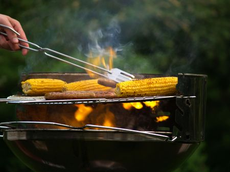 corn and sausages on a flaming barbecue