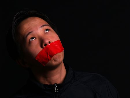 An Asian man held hostage with red tape over his mouth Stock Photo - 2612368