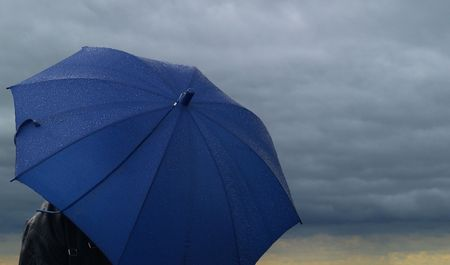 somber: Blue umbrella over a dark stormy cloud Stock Photo