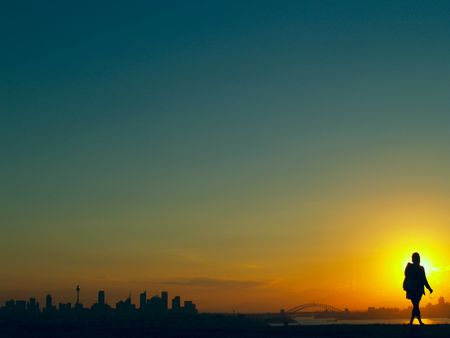 Sunset over Sydney, Australia with a woman standing in front of the sun enjoying the view photo