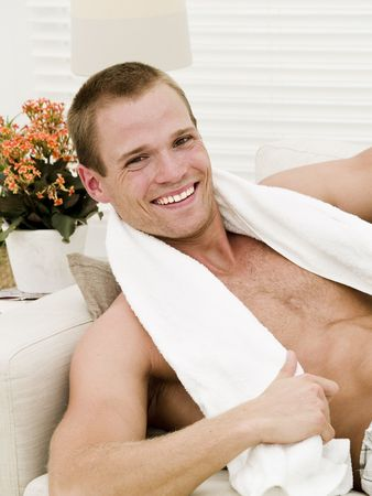 Muscular man with a towel getting a rest after working out photo