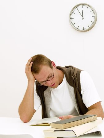 Een jonge student werkt aan zijn huiswerk, terwijl de klok tikt