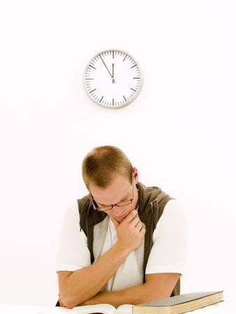 Een jonge student werkt aan zijn huiswerk bijna met zijn pauze om 12 uur
