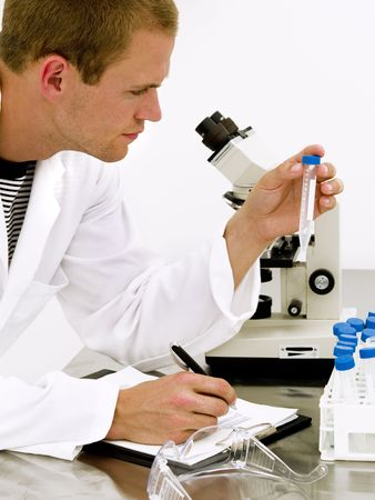 Male scientist looking at the flask with a microscope behind him Stock Photo