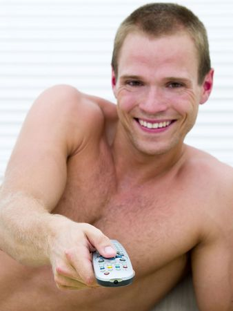 Muscular man lying on the sofa watching a funny movie (focus on remote) Stock Photo - 6628066