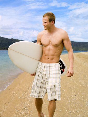 granola: Dude de surfista muscular camina en la playa buscando la gran ola