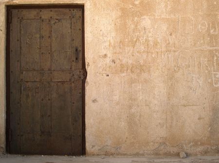 Old rusty door in a plastered wall with lots of copy space photo