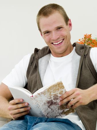 Young adult reading a book while hes lying on the couch photo