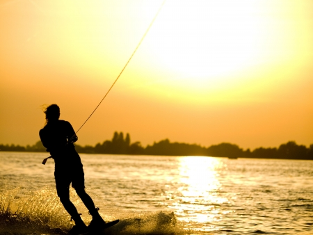 Girl is wakeboarding on a lake during a beautiful sunset