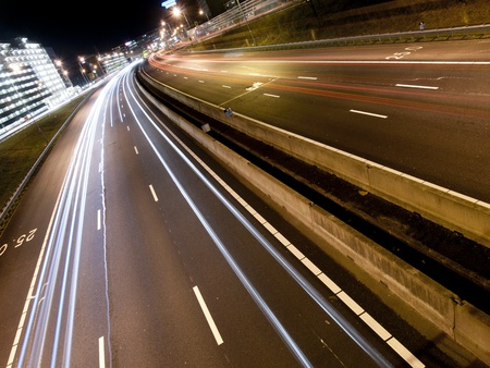 Long light trails from cars on a modern freeway photo