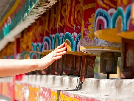 Female hand spinning the prayer wheels for good karma