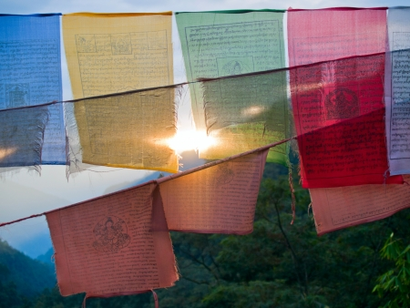 Setting sun shining through colorful prayer flags with the himalayan mountains in the back photo